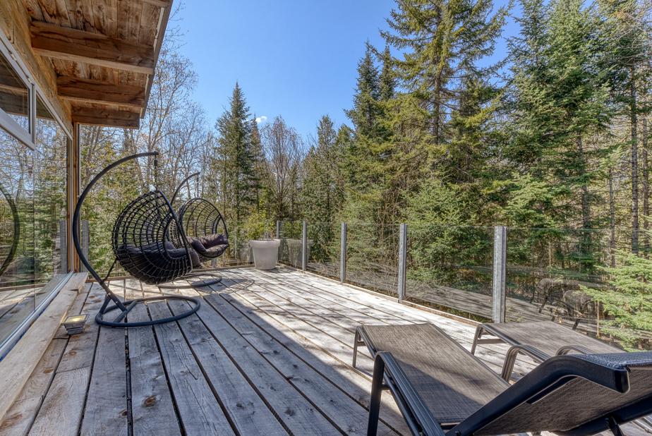Cette terrasse extérieure jouit d'un bel ensoleillement et offre une vue sur la nature. Elle se situe au-dessus de la véranda.