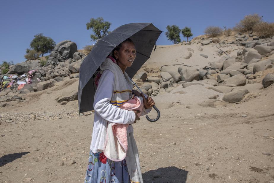 Une réfugiée avec son poupon après avoir franchi la rivière.