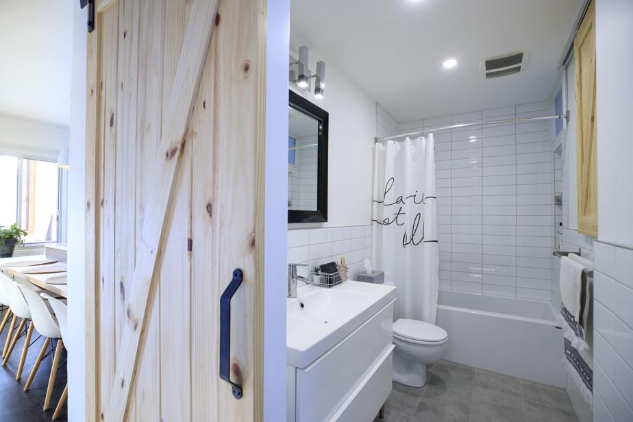 Dans la salle de bains refaite à neuf dans des tons neutres, une façade en bois clair coordonnée à la porte cache des tablettes. Chaque centimètre carré est exploité afin de pallier la suppression des rangements dans la salle à manger.
