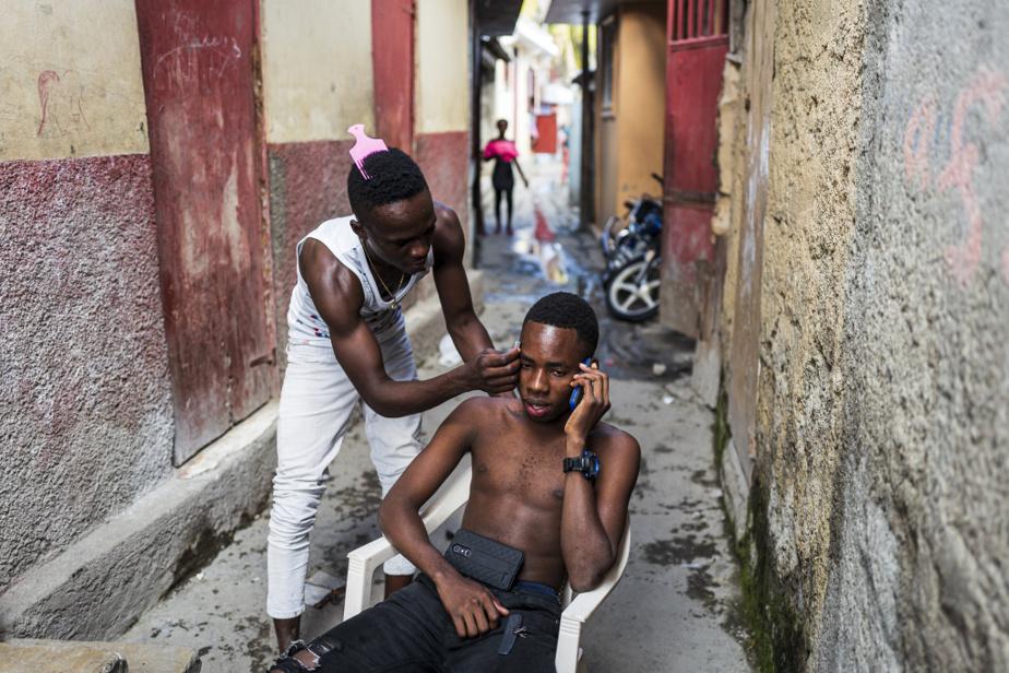 Un jeune homme se fait couper les cheveux dans les étroites allées du bidonville de Conassa.