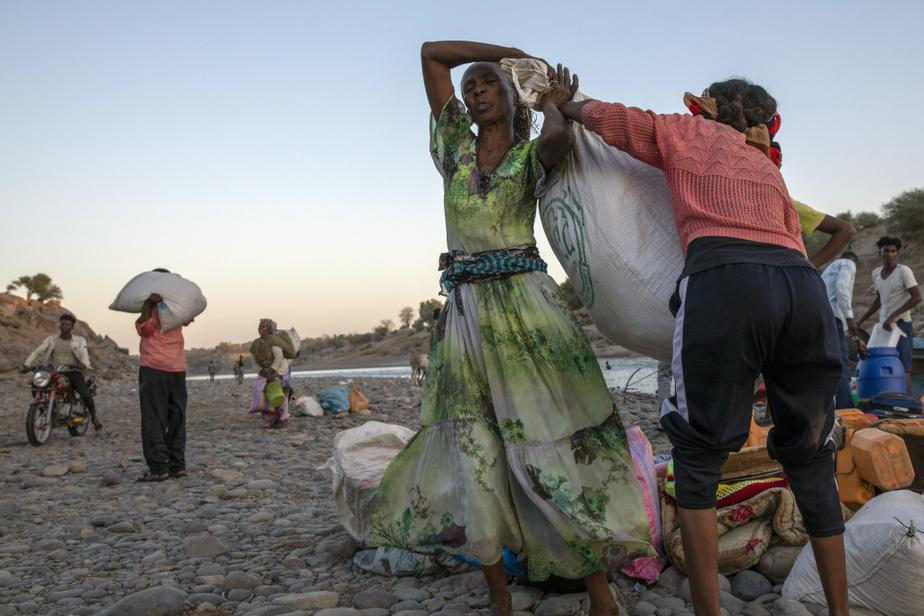 D'autres femmes traînent péniblement les possessions qu'elles ont pu transporter.