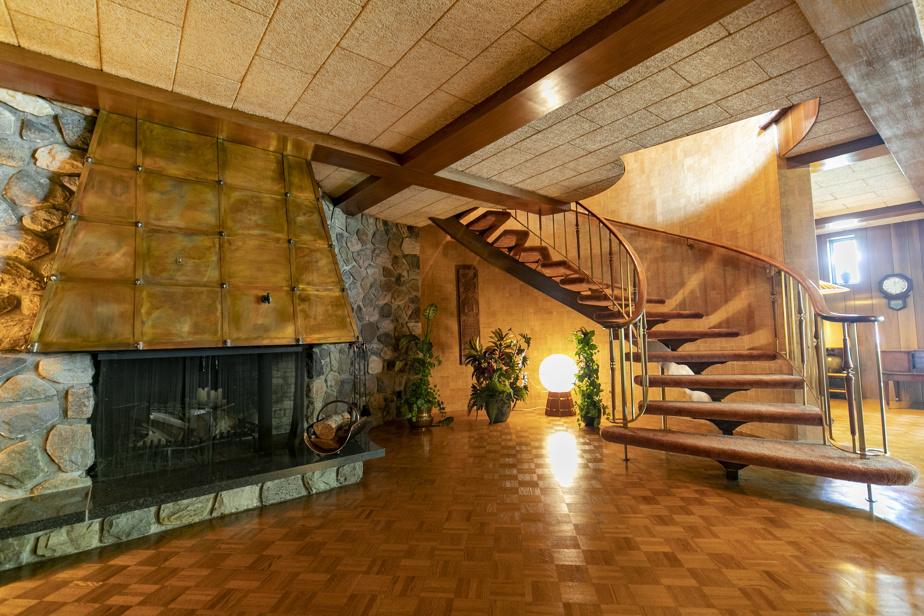 Un imposant escalier tout en rondeurs relie l'étage principal au sous-sol, où l'on retrouve un grand foyer en pierres et en cuivre.