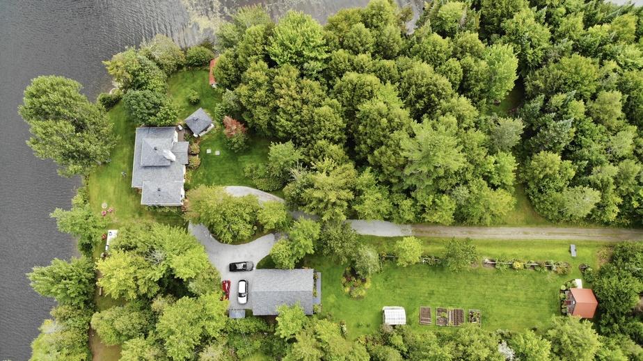 Vue des airs, avec la maison principale, le garage, la serre, le potager, la remise et le boisé dans lequel ont été disposées des œuvres d'art.