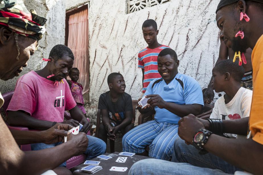Une famille joue aux cartes dans les étroites allées du bidonville de Conassa. Les perdants doivent porter des pinces, en guise de déshonneur.