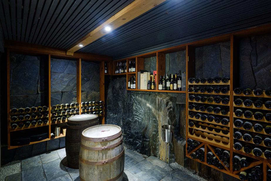 Une paroi naturelle de roc sert de mur principal à la cave à vin. Elle conserve la fraîcheur et l'humidité de la pièce. Les autres cloisons et le sol sont réalisés avec de l'ardoise trouvée sur le terrain.
