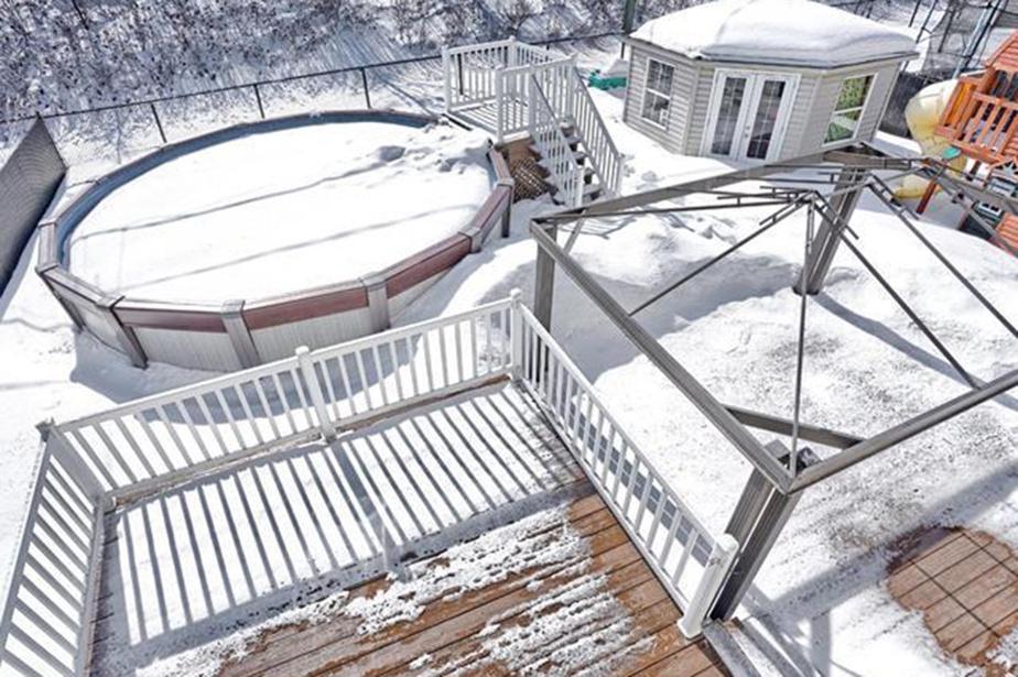 Une piscine hors terre chauffée et un cabanon se trouvent dans la cour.