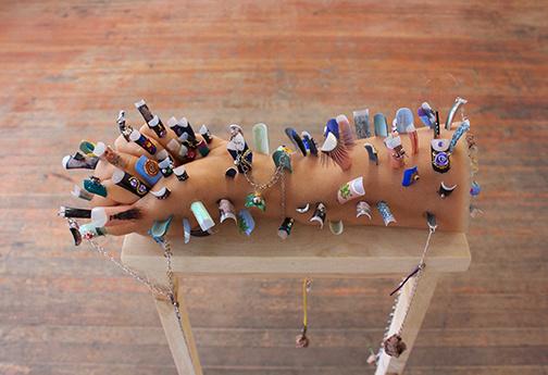Many, Looks, Work [De nombreux, looks, fonctionnent], 2017, Gabi Dao, ongles acryliques et accessoires, gélatine, maquillage, poussière, autres pièces de détritus, fil de cuivre, mica, argile, fils de connexion, chaîne de bijou, chaîne brisée d'un appareil d'éclairage, faux-cils, vernis à ongle, prune blanche séchée, fleurs séchées, pin noueux, dimensions variables. Vue d'installation à la Unit17, Vancouver.