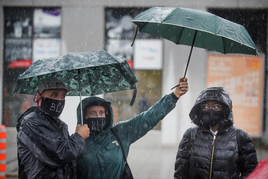 Manifestation pour le «définancement» de la police à Montréal. Des participants affichent leur soutien avec le fameux sigle de Black Lives Matter.