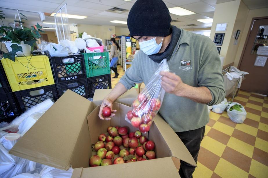 Carlos Flores, qui travaille aux Fourchettes, prépare des sacs de pommes pour les bénéficiaires.