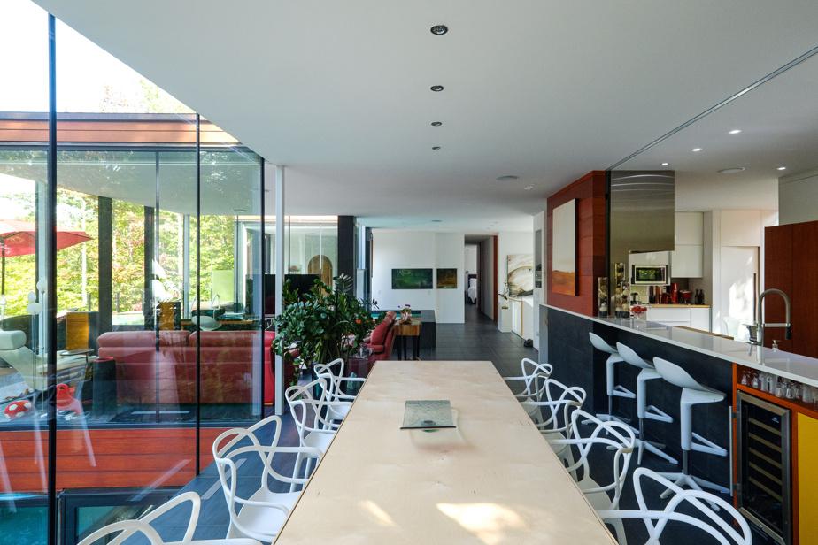 Du bout de la salle à manger, on voit le salon en retrait et on aperçoit la chambre principale tout au fond. Le propriétaire a installé un rail au-dessus de l'îlot de cuisine, afin d'y mettre des panneaux de bois coulissants afin de fermer l'espace au besoin.