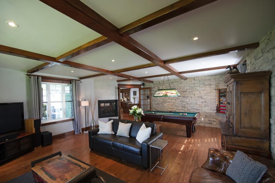 Chaque pièce située côté fleuve possède une vue sur l'eau. Ici, le salon est relié à la salle de jeux, où trône une table de billard.