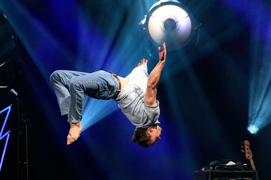 Sur la scène principale des Francos de Montréal, un membre du groupe Bleu Jeans Bleu s'improvise acrobate.