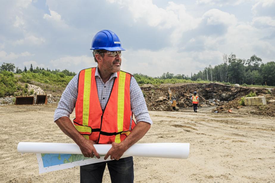 Éric Desaulniers, président-directeur général de Nouveau Monde Graphite, regarde une carte du projet sur la parcelle test du projet.