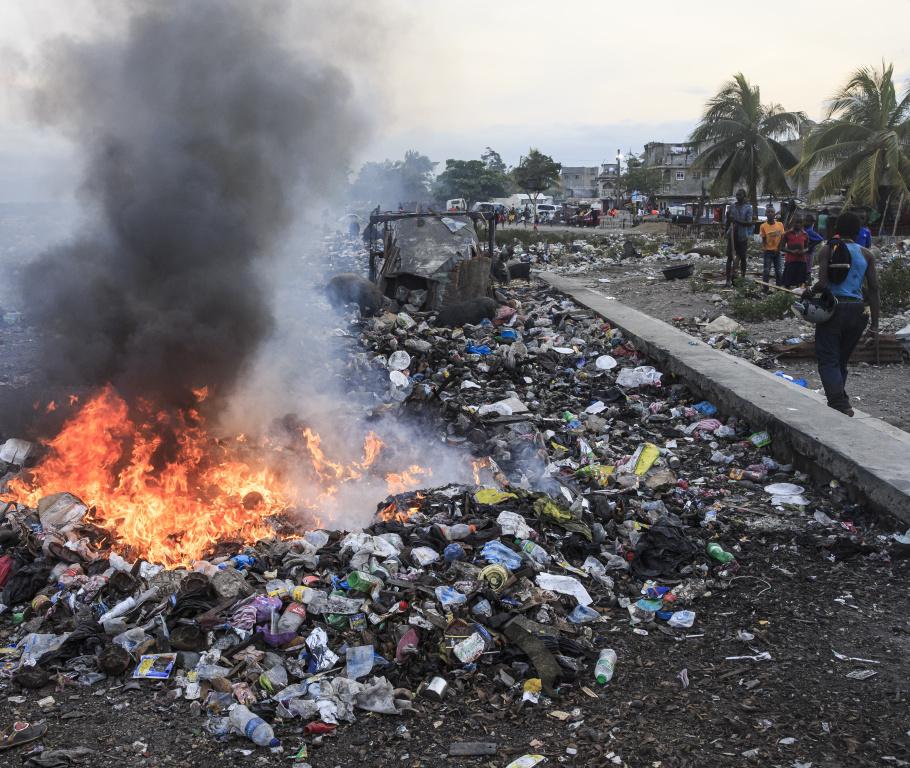 La gestion des déchets est un problème criant à Cap-Haïtien, particulièrement dans les bidonvilles. Faute d'enlèvement des ordures, celles-ci sont jetées sur les berges et souvent brûlées, ce qui alimente l'épais nuage de fumée.