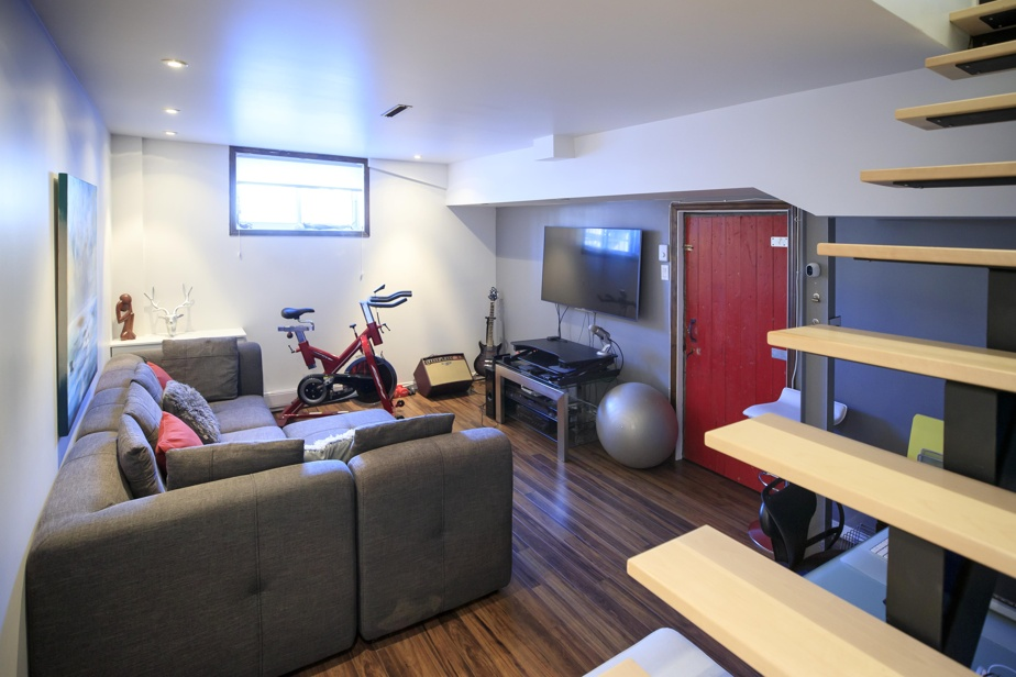 Le sous-sol entièrement fini comprend deux chambres, une salle de bains et un séjour incluant un coin bureau. André Gagné voulait un escalier ouvert pour plus de légèreté et de clarté dans l'espace. «La structure a été fabriquée par un soudeur, et on l'a rentrée par la petite fenêtre!», se souvient-il.