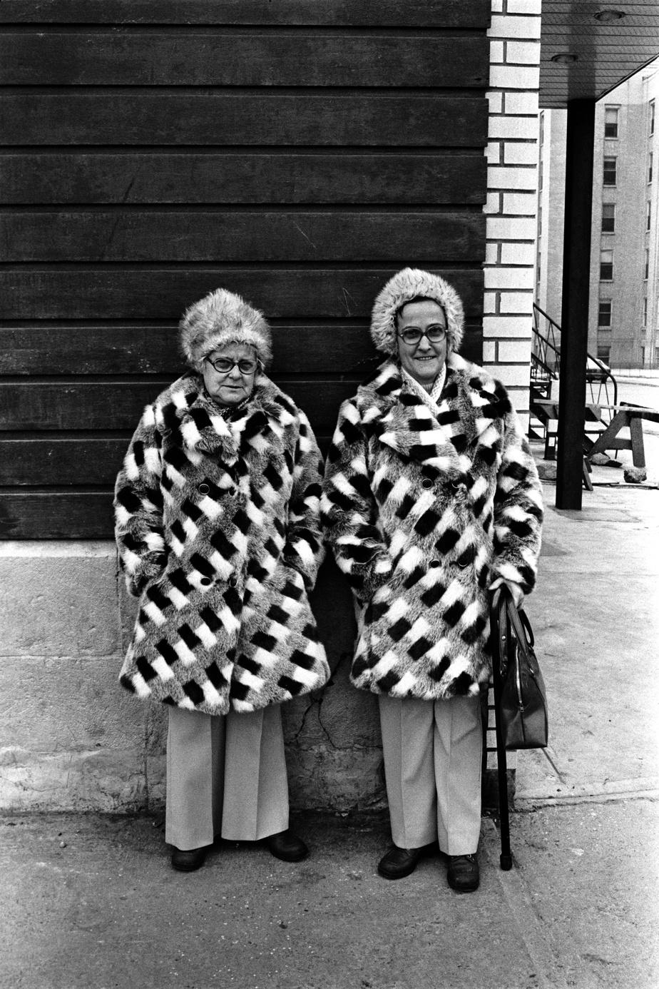 Des femmes arborent le même manteau, au coin du boulevard Dorchester et de la rue Saint Laurent, à Montréal, en 1975.