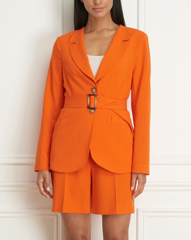 Veston avec ceinture et grandes poches tangerine (525$) et short mi-cuisse assorti (225$)