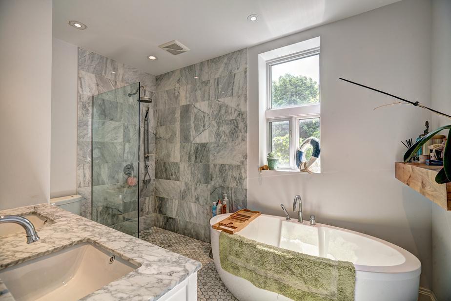 La maison comprend trois salles de bains et une salle d'eau. Les enfants installés à l'étage supérieur se partagent celle-ci, refaite au goût du jour, mais en marbre de Carrare afin de répondre au style classique et élégant de la propriété. La douche à l'italienne et la baignoire autoportante allègent l'espace.