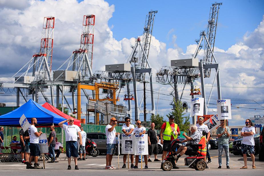 19août2020. Des débardeurs reçoivent l'appui d'un passant en triporteur alors qu'ils se trouvent sur la ligne de piquetage au port de Montréal.