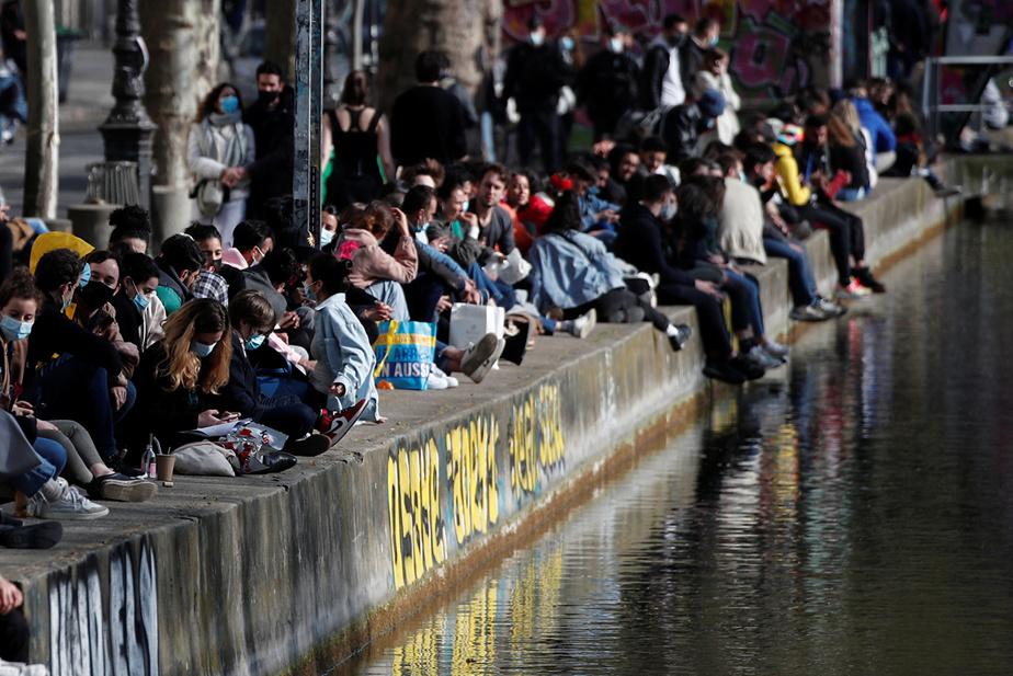 Des Parisiens profitent d'une journée ensoleillée sur le bord du canal Saint-Martin avant la tombée du couvre-feu.