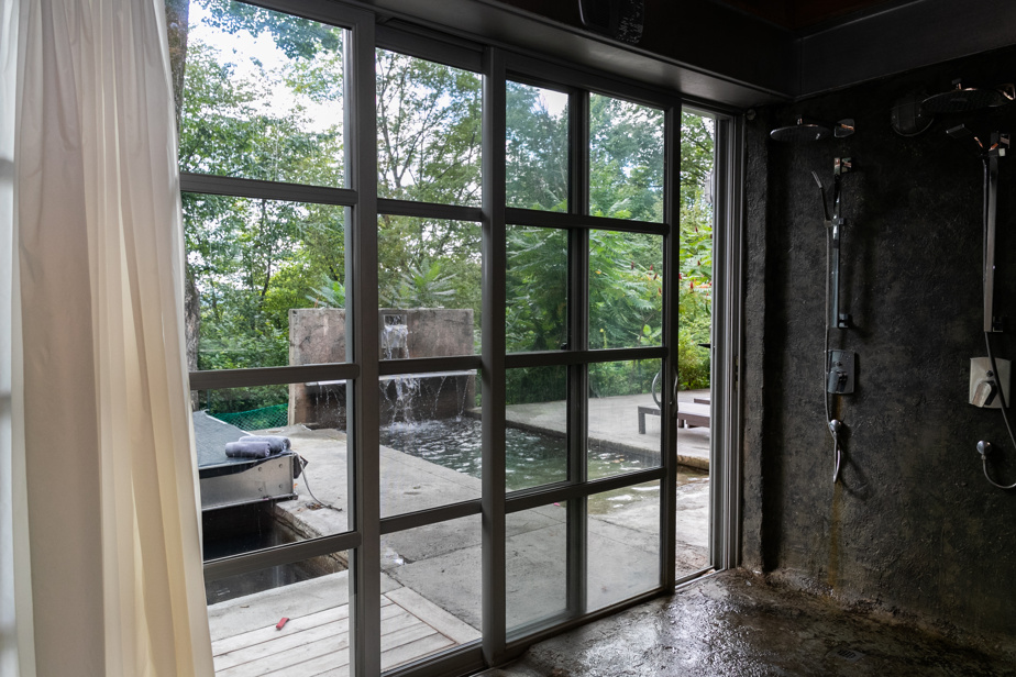 La salle de bains attenante à la chambre principale donne directement sur la terrasse, près du spa et de la piscine. Elle est composée d'une baignoire encastrée dans le sol de béton, d'une douche double et d'un grand meuble-lavabo. La toilette est séparée, comme dans chaque salle de bains.