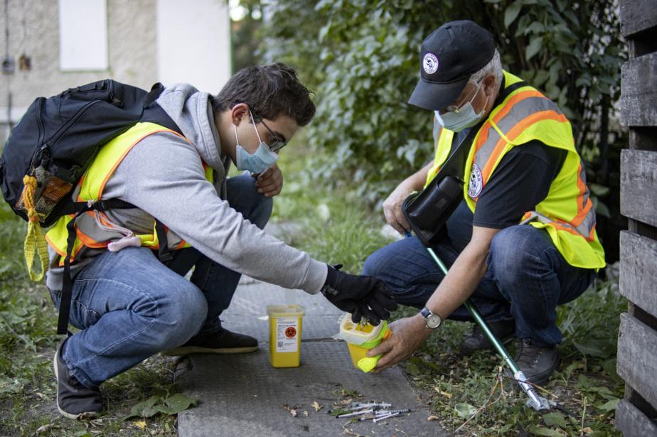Les bénévoles Matteo Gerinario et Rob Shaw ramassent des seringues souillées dans la cour d'une maison abandonnée. Dans ces quartiers pauvres de Winnipeg, des gangs de rue autochtones se disputent le marché de la drogue.