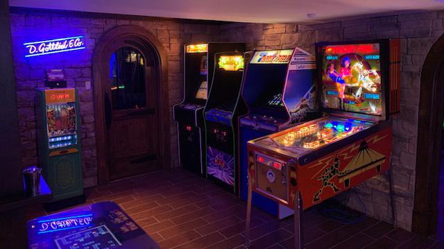 Une partie de la magnifique salle d'arcade de Stephane Tennier. On aime?: la brique, les portes, les néons, les sièges. Dans une pièce attenante, on trouve un bar complet et une scène de spectacle. Wow?! Découvrez la salle entière dans la vidéo suivante.
