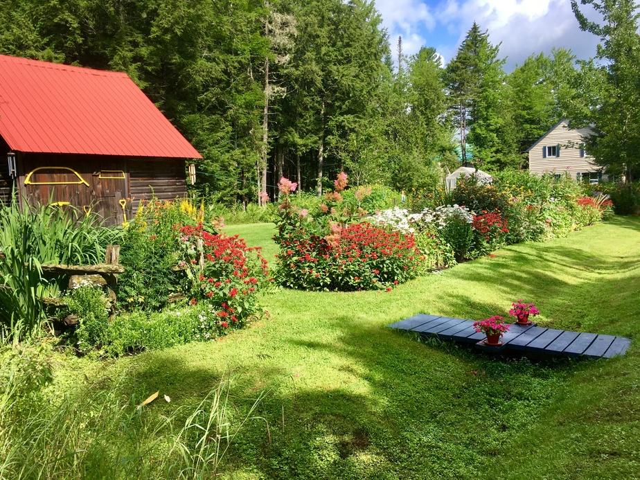 Jacques Duquette et Réjean Rousseau passent des heures, chaque été, à enjoliver les lieux avec des dizaines de plantes et de fleurs. À gauche, la remise avec sa vieille porte à coulisse d'origine.