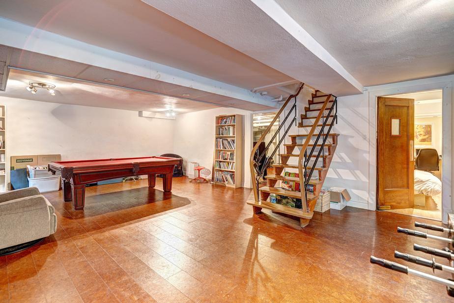 Le sous-sol a été aménagé en espace de loisirs; une chambre et une salle de bains ont aussi été ajoutées. Ces deux pièces étaient destinées à la fille aînée de la famille, mais pourraient aussi bien servir de suite pour les invités.