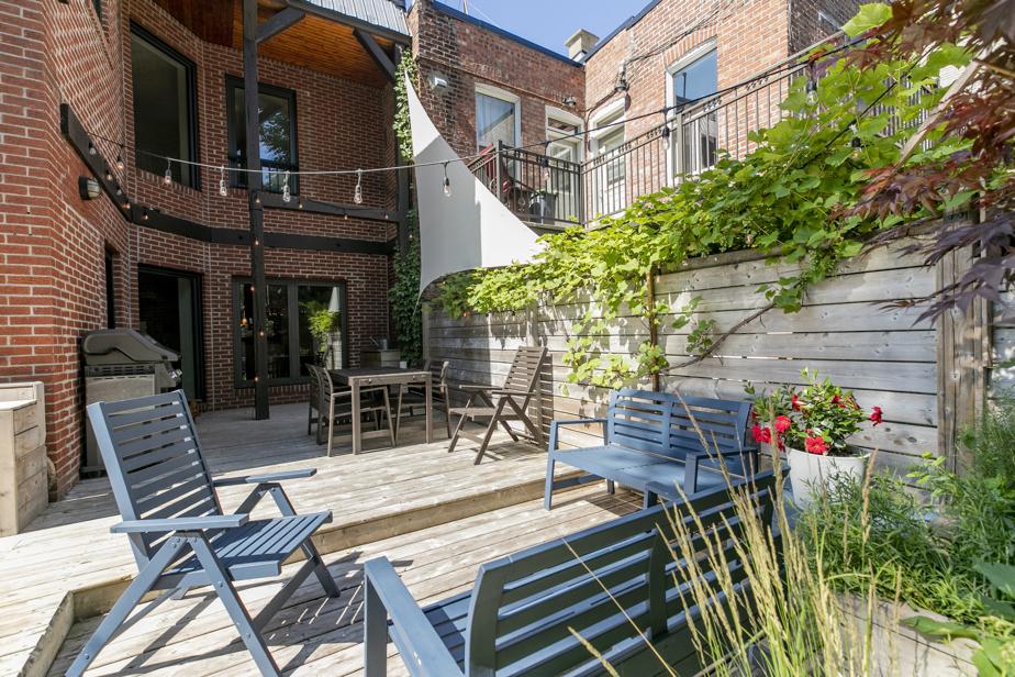 La cour arrière est très privée. La terrasse en bois est posée sur une solide dalle de béton. La zone salle à manger s'organise près de la cuisine, tandis que le coin salon est aménagé en contrebas.
