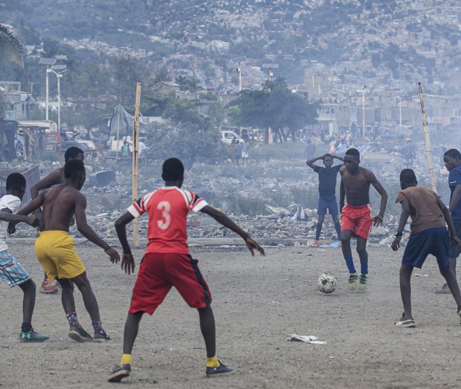Des jeunes du quartier terminent leur journée par une partie de soccer dans un épais nuage de fumée émanant d'un feu de déchets à proximité.