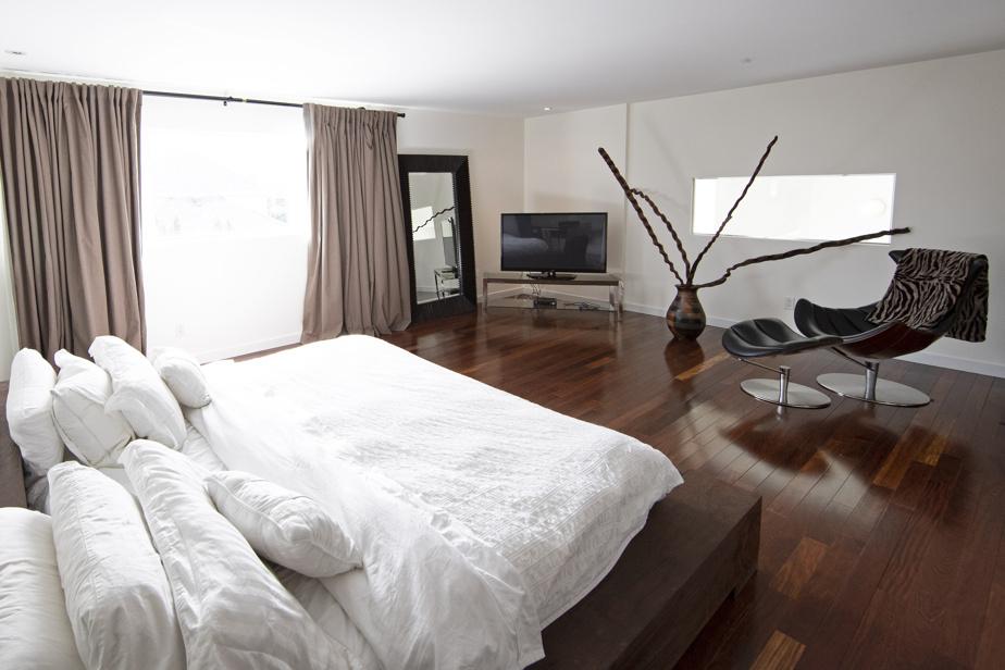 La chambre principale, très spacieuse, avec salle de bains attenante. Notez la fenêtre rectangulaire du fond, qui offre une vue sur l'intérieur de la maison.