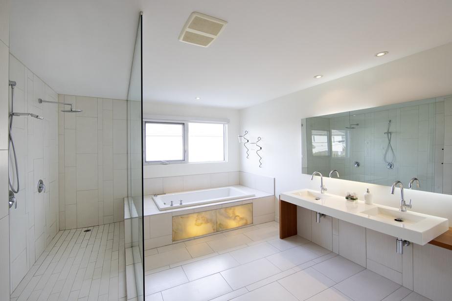La salle de bains principale, spacieuse également, joue sur les blancs. L'emplacement et l'angle des fenêtres ont été pensés pour préserver l'intimité des occupants sans avoir besoin de recourir aux rideaux.