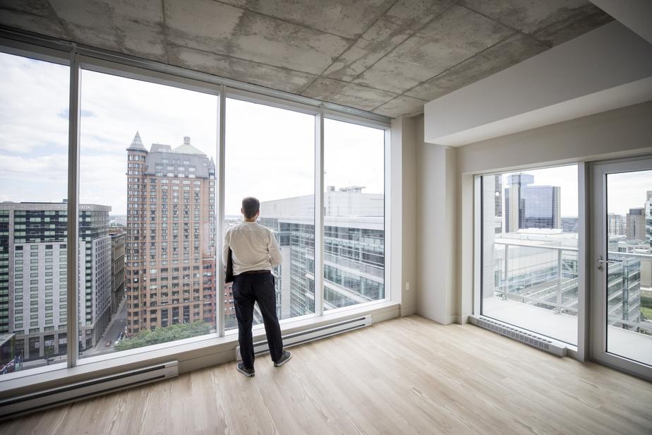 D'immenses fenêtres bordent les appartements. Elles laissent entrer la lumière et permettent d'avoir une belle vue sur les environs. StevenRicciardi, qui a guidé le photographe, admire le paysage urbain du haut du 19eétage.