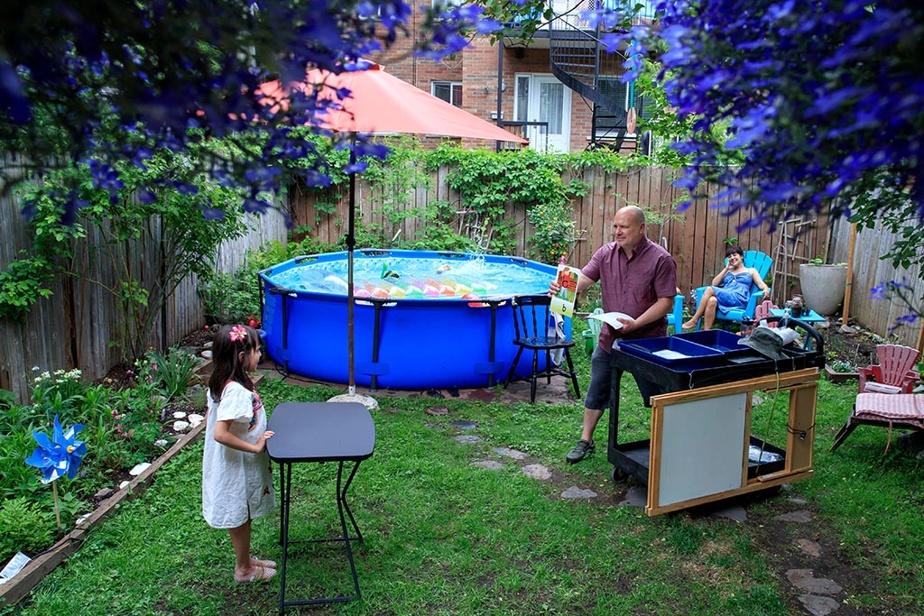 28mai2020. Depuis quelques semaines, Marc Brunette passe de maison en maison pour enseigner à ses élèves de la maternelle. À côté de la piscine, il donne ici des leçons à Eloïse Pin, 6ans, sous le regard attendri de sa maman, Chloe Spandonide.