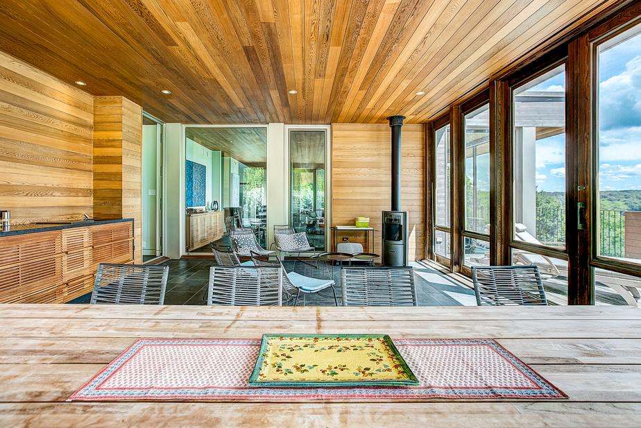 Dès le mois de mars, on peut s'installer dans la véranda équipée de vitres et d'un foyer au bois Stûv. Le buffet muni d'un évier, d'un tiroir réfrigérant et d'un congélateur fait office de cuisine d'été.