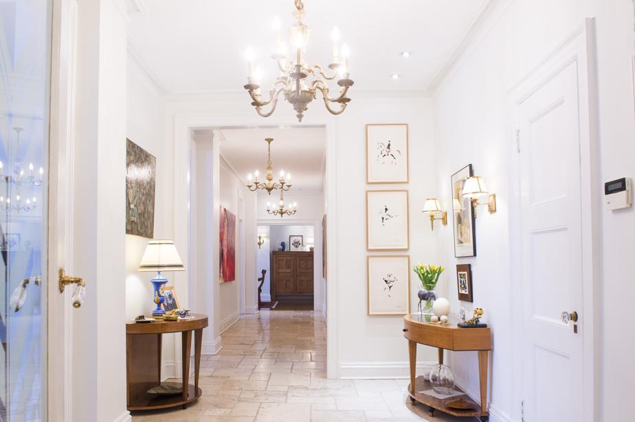 Voici la vue de l'appartement une fois le seuil passé. Le vestibule et le couloir sont recouverts de travertin alors que les parquets des pièces sont en lattes de bois.