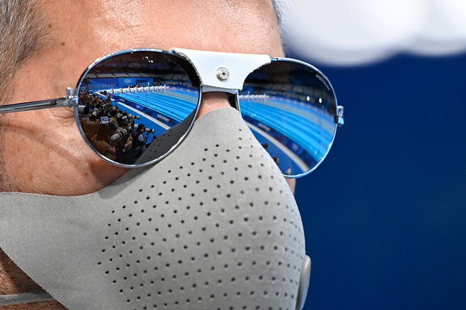 Réflexion de la piscine dans les lunettes d'un photographe juste avant la finale du 100m papillon masculin