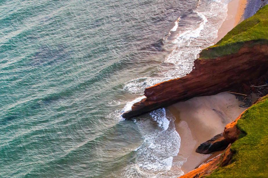 De petites anses formant de magnifiques plages privées se succèdent entre les parois rocheuses de l'Étang-des-Caps, aux Îles-de-la-Madeleine.