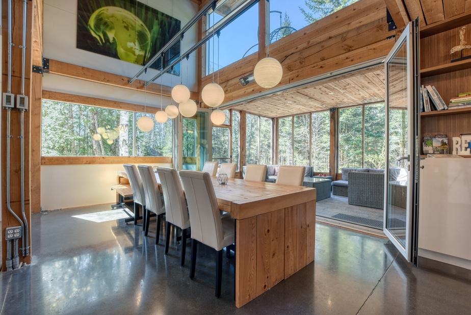 La salle à manger peut accueillir plusieurs convives. Les grandes portes-fenêtres donnent accès à une spacieuse véranda trois saisons, fermée par des moustiquaires.