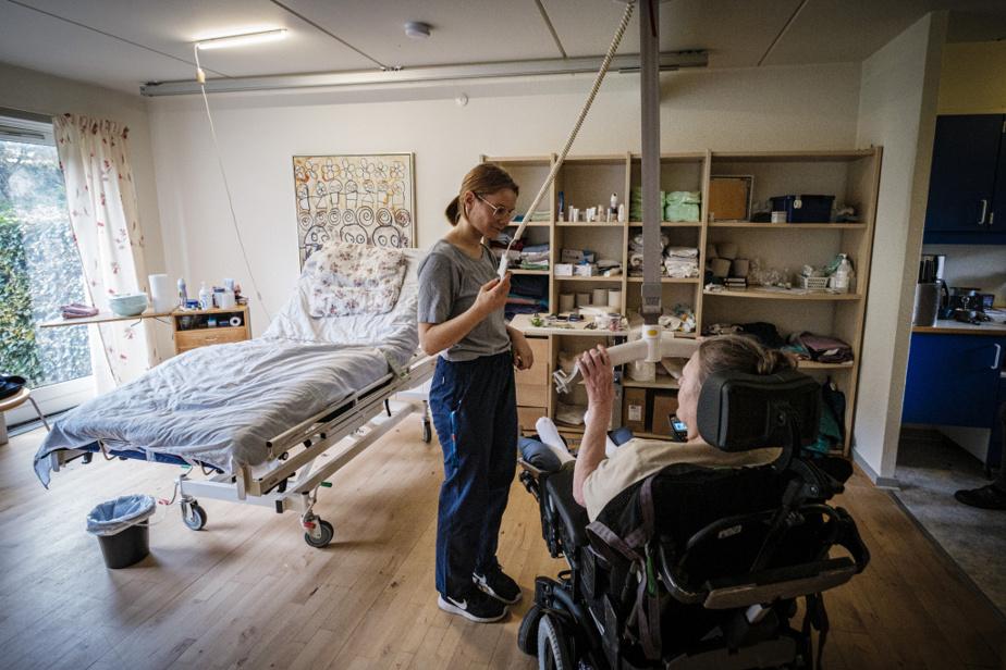 Alitée, Lis Skadhauge Vendelboe se fait transférer vers son fauteuil électrique par l'infirmière Amalie Lund Madsen.
