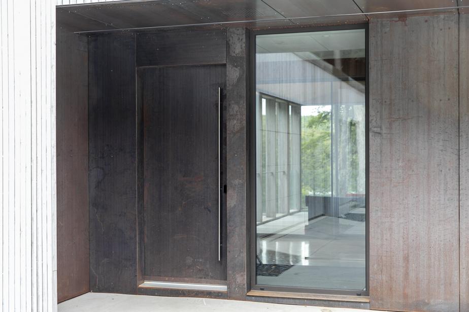 Située à l'abri du vent, l'entrée est habillée elle aussi d'une plaque de corten pour rappeler le traitement du rez-de-jardin.