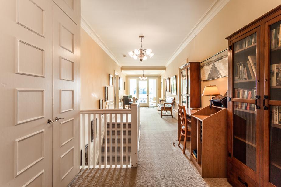 Nous voici dans le hall de l'étage, qui compte cinq chambres et trois salles de bains.