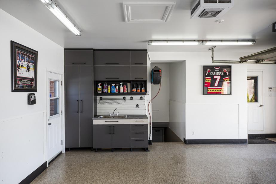 Une section du garage comprend un évier et des armoires. S'y trouve tout le nécessaire pour laver et faire l'entretien de voitures et de motos.