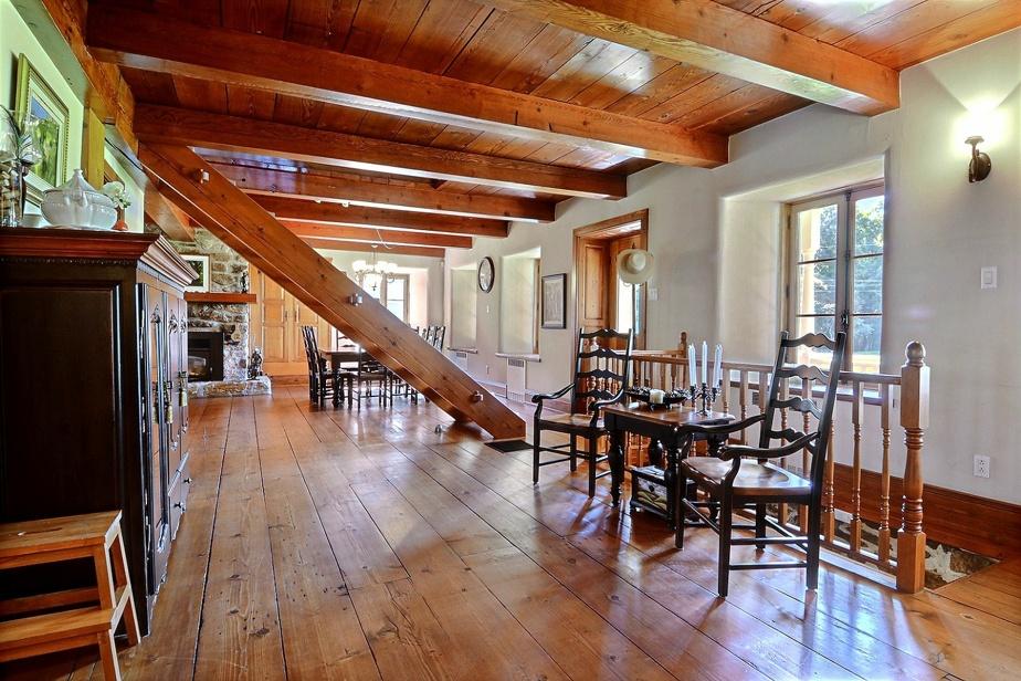 On accède à l'étage des chambres par cet escalier de meunier, réalisé à la manière d'antan. À l'arrière-plan, on remarque la salle à manger, près d'un foyer.