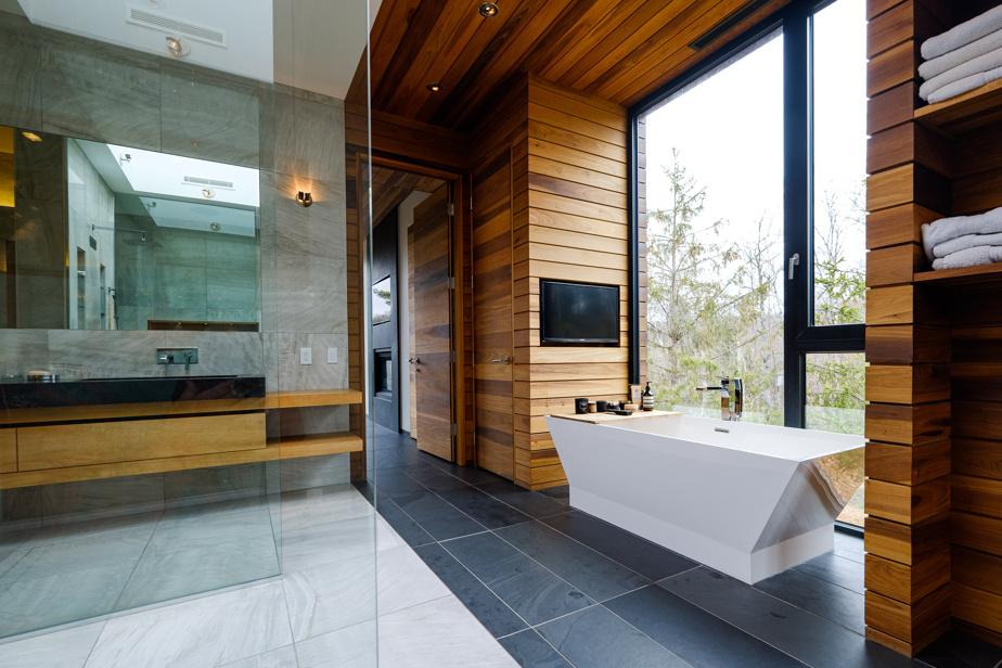 La maison compte quatre salles de bains. La plus grande, celle des parents, propose une immense douche avec pommeau à effet de pluie. Le sol est différent ici avec ses carreaux marbrés importés d'Italie. La baignoire autoportante est directement devant la fenêtre. Comme dans la cuisine, les lavabos sont en pierre naturelle.