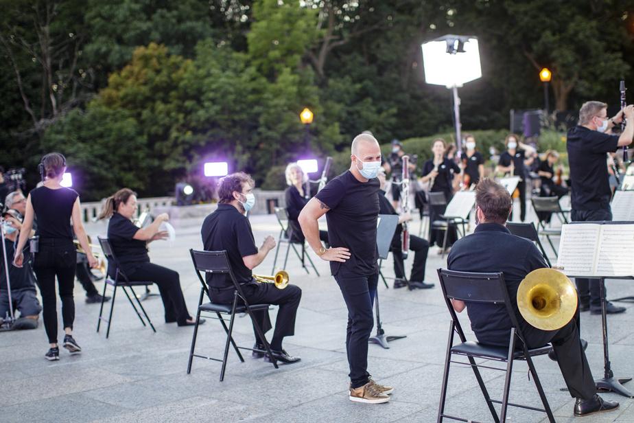 Après des mois difficiles où les prestations ont été rares, les musiciens et musiciennes de l'Orchestre Métropolitain se sont retrouvés sur le mont Royal en juillet dernier. Ici, le chef principal, Yannick Nézet-Séguin, discute avec les musiciens de l'orchestre, masqués pendant les pauses de l'enregistrement de la prestation musicale.