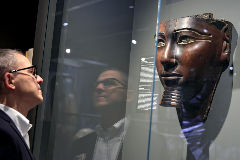 Stéphane Aquin devant un masque funéraire égyptien datant de 664 à 525 avant l'ère chrétienne. Collection MBAM.