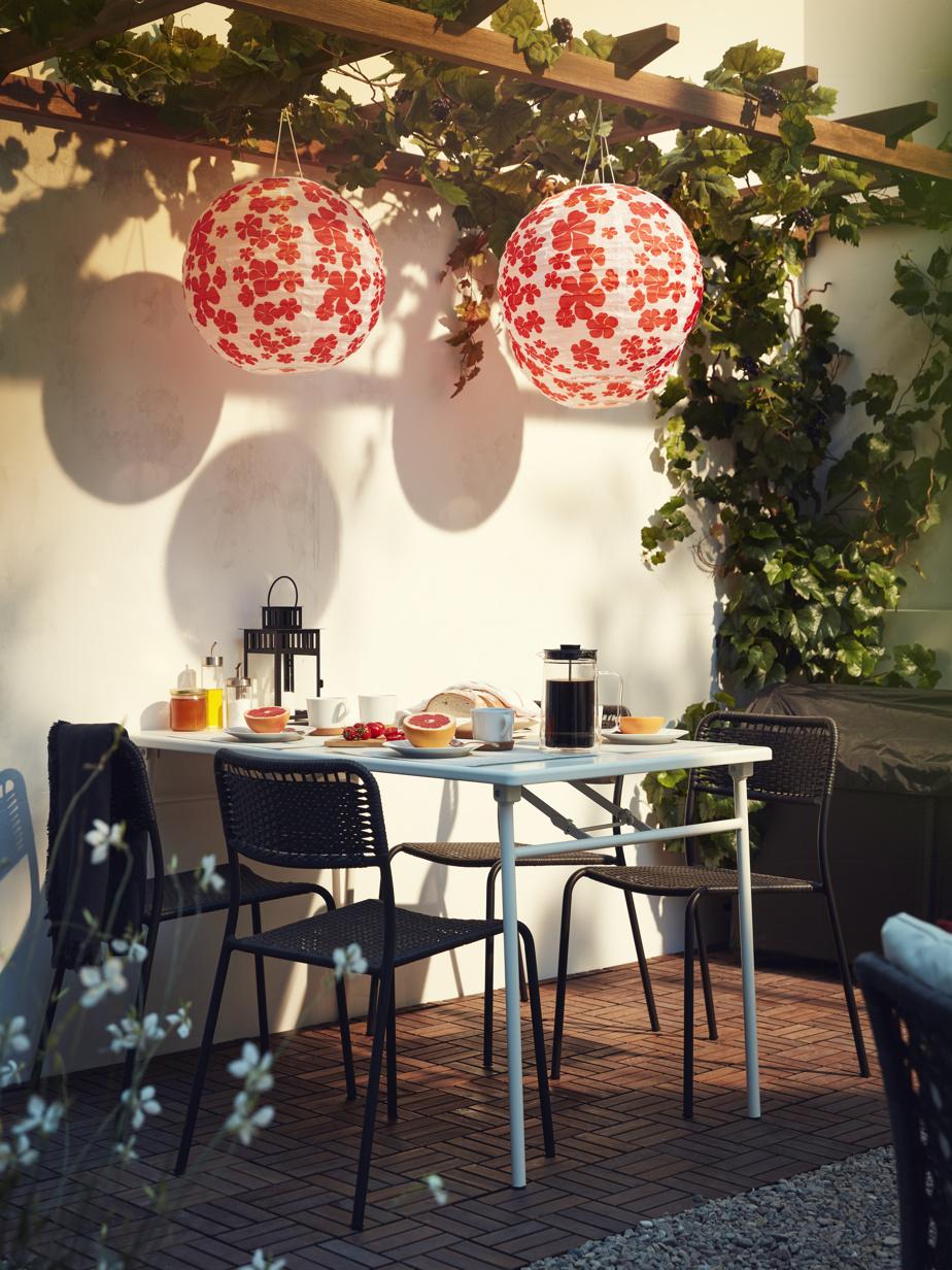 Quelques touches de couleurs et des textures diversifiées rendent la terrasse invitante. Les lampes suspendues à énergie solaire, comme celles-ci au motif fleuri, font le plein d'énergie le jour et s'allument le soir venu, indique Heena Saini, spécialiste des relations publiques sur le plan commercial chez IKEA Canada.