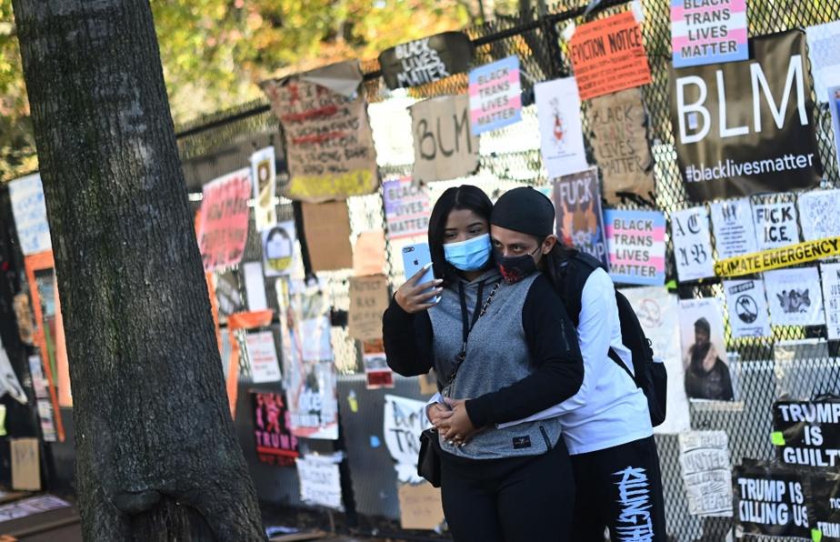 Un jeune couple devant une clôture du square Lafayette couverte d'affiche BLM.
